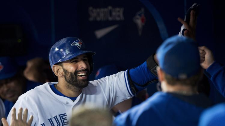 Toronto Blue Jays Jose Bautista, left, celebrates with teammates in the dugout after hitting a solo home run against the Boston Red Sox during seventh-inning baseball game action in Toronto, Wednesday, July 23, 2014. (AP Photo/The Canadian Press, Nathan Denette)