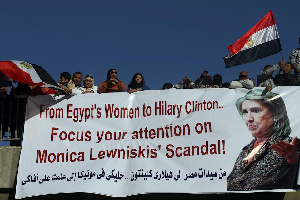 Egyptian pro-military ruling council supporters wave by national flags over a banner with a message to US Secretary of State Hillary Clinton, during their rally to support the council in Cairo, Egypt Friday, Dec. 23, 2011. (AP Photo/Ahmed Ali)