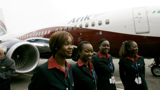 FILE-  In this April 26, 2007 file photo, cabin crew members with Arik Air stand in front of a new Boeing 737-700 purchased by Arik Air, at Boeing Field in Seattle, Washington. Arik, Nigeria's largest airline, announced Thursday, Sept. 20, 2012 that it has halted all domestic flights alleging that government corruption made it impossible for it to fly. Arik ending its domestic flights will add further chaos to Nigeria's aviation industry. The country is still trying to recover from an airline crash that killed more than 160 people in June.(AP Photo/Ted S. Warren, File)