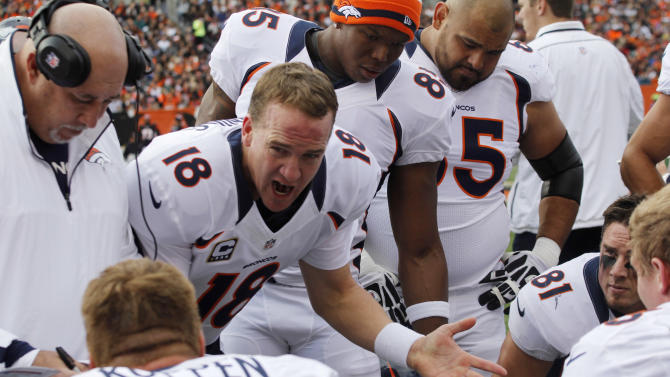 Denver Broncos quarterback Peyton Manning (18) talks to players on the bench in the first half of an NFL football game against the Cincinnati Bengals, Sunday, Nov. 4, 2012, in Cincinnati. (AP Photo/Tom Uhlman)