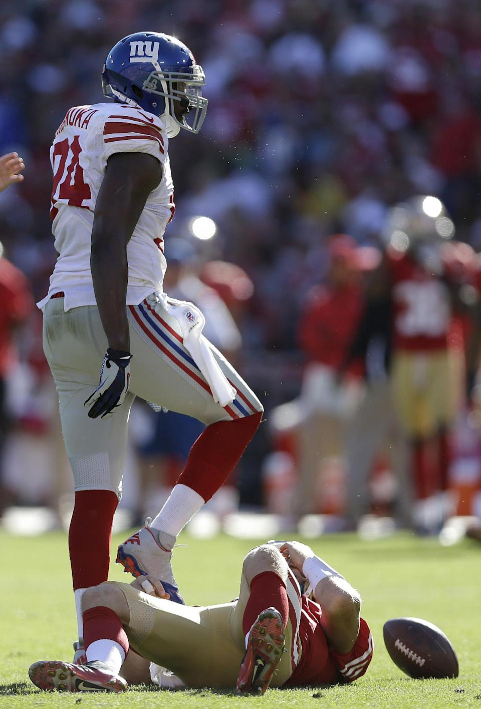 New York Giants outside linebacker Mathias Kiwanuka (94) stands over San Francisco 49ers quarterback Alex Smith (11) after sacking him during the fourth quarter of an NFL football game in San Francisco, Sunday, Oct. 14, 2012. The Giants 26-3. (AP Photo/Marcio Jose Sanchez)