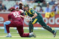 Adam Voges (R) steers a ball past West Indies fielder Kieron Pollard in the one-day international at the MCG on February 10, 2013. The stand-in batsman hit a maiden ODI century to lift Australia to a fighting 274 for five in the fifth and final match