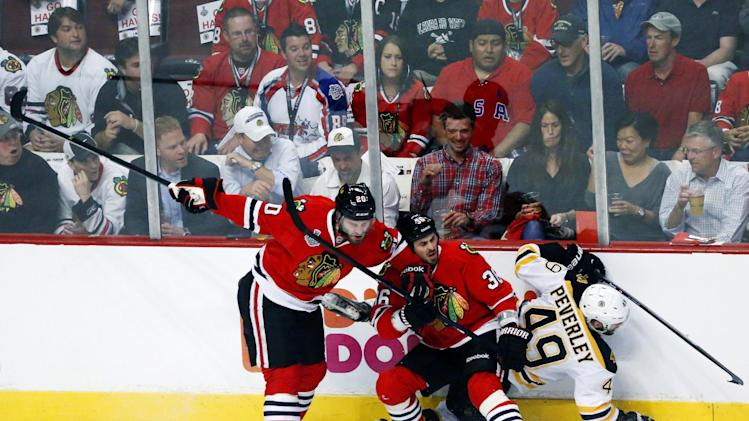 Chicago Blackhawks left wing Brandon Saad (20) and center Dave Bolland (36) collide with Boston Bruins center Rich Peverley (49) during the first period of Game 1 in their NHL Stanley Cup Final hockey series, Wednesday, June 12, 2013 in Chicago. (AP Photo/Charles Rex Arbogast)
