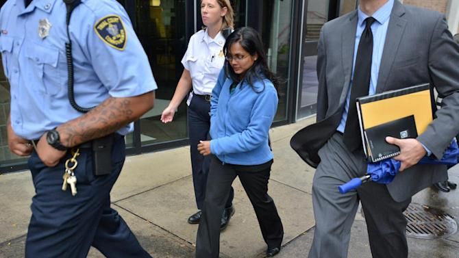 Annie Dookhan, center, is escorted from a Boston courthouse after refusing to testify in a drug case against Shawn Drumgold, Wednesday, Oct. 10, 2012. A lawyer for Shawn Drumgold asked a judge in Roxbury District Court to dismiss two drug charges against her client because Dookhan's initials appear on a drug analysis form indicating she tested the suspected cocaine and heroin. Dookhan is accused of faking drug results, forging signatures and mixing samples a state police lab. State police say Dookhan tested more than 60,000 drug samples involving 34,000 defendants during her nine years at the lab. (AP Photo/Josh Reynolds)
