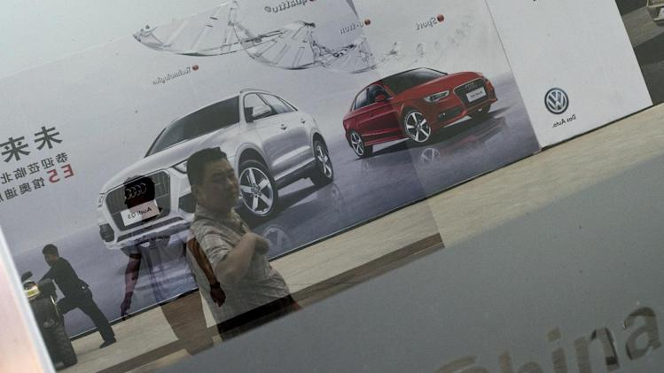 Reflected in a glass door, visitors walk past Audi's car advertisement at the China Auto show in Beijing, Wednesday, April 23, 2014. Luxury automakers, like their mass-market counterparts, are looking to China to drive future growth and are investing heavily to gain or expand a foothold in its market. (AP Photo/Alexander F. Yuan)