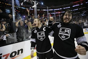 Los Angeles Kings right wing Dustin Brown, left, and teammate defenseman Drew Doughty celebrate after beating the New York Rangers in overtime in Game...