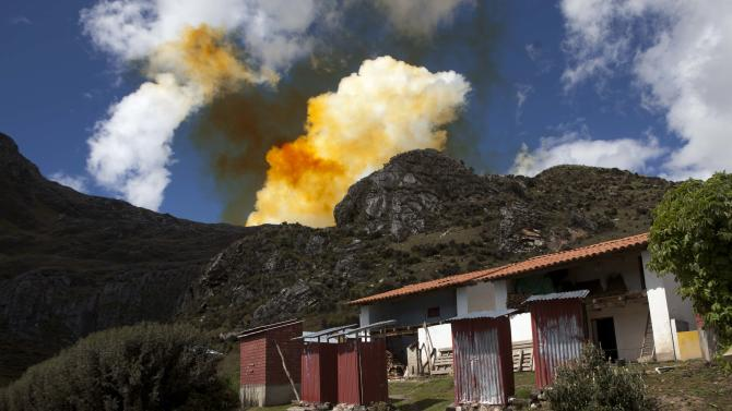 """In this May 16, 2013 photo, Lidia Zorilla returns to her home to get her mule in San Antonio de Juprog, Peru, as an orange cloud rises above the open-pit Antamina mine. On the edge of the nearly half mile-deep pit, blasts hurl skyward a blood-orange dust that laces the village's pastures and fields with heavy metals, contaminating people, crops and livestock. """"It penetrates your skin, like ashes from a wood fire,"""" says Zorilla, a 34-year-old. (AP Photo/Martin Mejia)"""