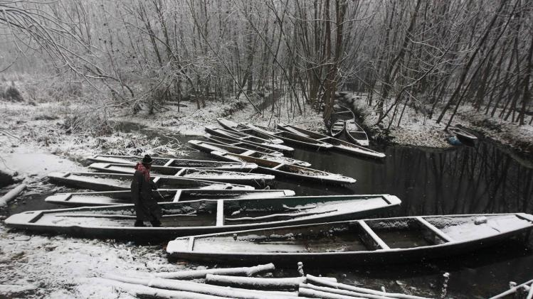 A Kashmiri man walks over snow covered parked boats during the season's first snowfall on a cold winter morning in Srinagar
