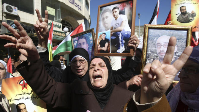 Women chant slogans, give the victory sign and display photographs of detained persons during a rally calling for the release of Palestinian prisoners jailed in Israel, in the West Bank city of Nablus, Monday, Feb. 18, 2013. Israel is holding some 4,500 Palestinians for charges ranging from throwing stones to undertaking deadly militant attacks. Their incarceration is a sensitive issue for Palestinians, who see them as heroes of the Palestinian liberation struggle. (AP Photo/Nasser Ishtayeh)