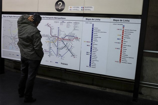 A commuter looks at a map of train routes at a subway station in downtown Sao Paulo