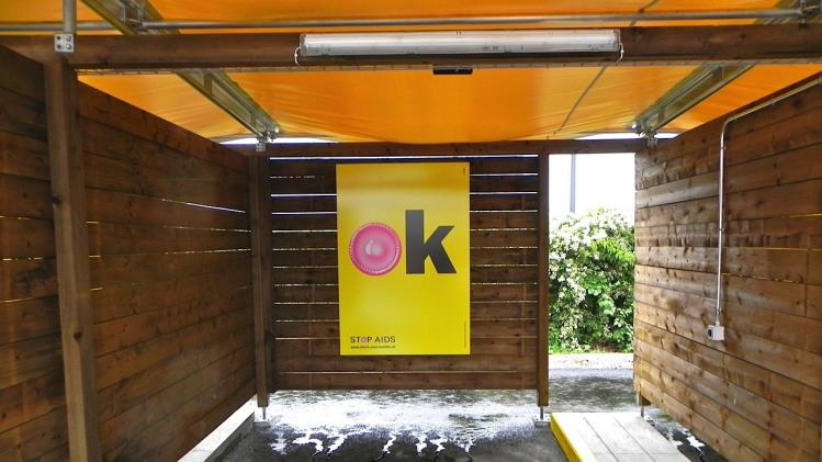 """In this Saturday, Aug. 24, 2013 photo, a poster hangs in an open, wooden, garage-style """"sex box"""" in Zurich, Switzerland. Prostitutes will be concentrated in a small city park built for more than USD $2 million in the Altstetten area of Zurich. It officially opens for business Monday. Prostitution is legal in Switzerland, but Zurich restricts it to certain areas, and is experimenting with the drive-in facilities to relocate the activity and improve safety and sanitation. The public had its first view of the completed facilities on Saturday. (AP Photo/John Heilprin)"""