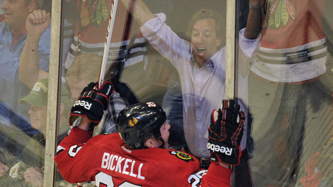 Chicago Blackhawks' Bryan Bickell (29) crashes into the boards while celebrating his game-winning goal against the Minnesota Wild during overtime in Game 1 of an NHL hockey Stanley Cup playoff series Tuesday, April 30, 2013, in Chicago. The Blackhawks defeated the Wild 2-1. (AP Photo/Jim Prisching)