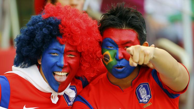 South Korea fans pose before the 2014 World Cup Group H soccer match between South Korea and Algeria at the Beira Rio stadium in Porto Alegre