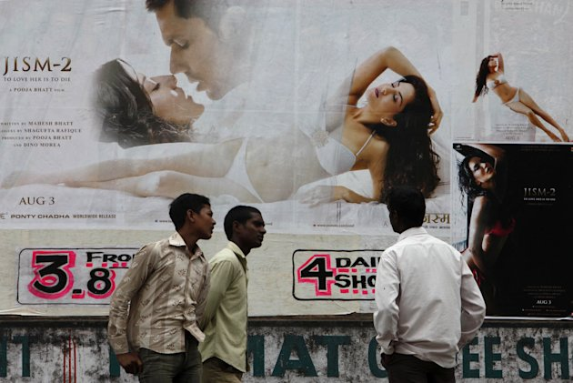"An Indian man watches a poster of Bollywood film ""Jism 2"" displayed outside a cinema in Hyderabad, India, Thursday, Aug. 2, 2012. ""Jism 2"" stars a hard-core porn actress, and it does have that pesky title. But it's not a porn movie. Bollywood is certainly not ready for that. The film, which will be released across India on Friday, is pushing the ever-widening sexual boundaries enjoyed by many in urban India. (AP Photo/Mahesh Kumar A.)"