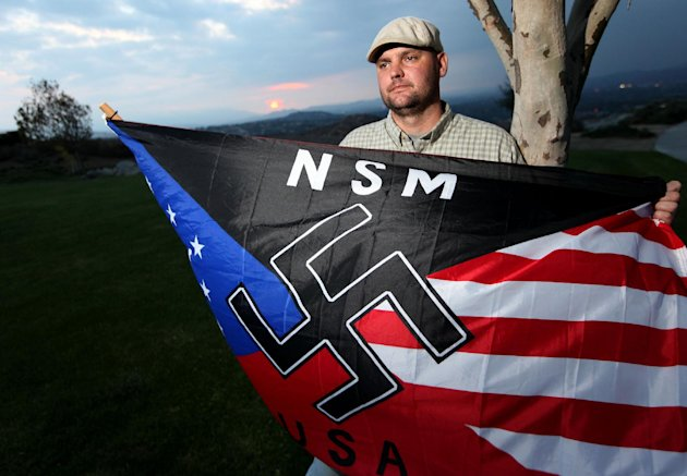 FILE - In this Oct. 22, 2010 file photo, Jeff Hall holds a Neo Nazi flag while standing at Sycamore Highlands Park near his home in Riverside, Calif. On Tuesday, Oct. 30, 2012, the trial begins in juvenile court for the 10-year-old boy charged with murder for shooting Hall, his white supremacist father while he slept on the couch in 2010. The child told investigators he killed his father with a gun kept unlocked in the family&#39;s home because he was tired of his father beating him and his stepmother. (AP Photo/Sandy Huffaker, File)