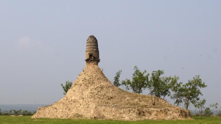 An ancient tower is seen balancing on the top of a dirt hill, with its base slightly eroded, along a grassland in Qixian county