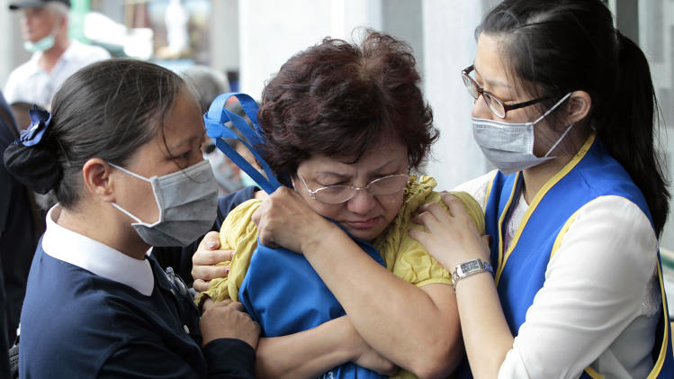 A relative of a victim in the TransAsia Airways flight GE222 crash is consoled during a funeral service on the Taiwan island of Penghu, Friday, July 25, 2014. Stormy weather on the trailing edge of Typhoon Matmo was the likely cause of the plane crash that killed more than 40 people, the airline said Thursday. (AP Photo/Wally Santana)