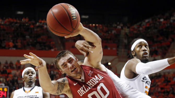 Oklahoma's Ryan Spangler loses the ball as he is fouled by Oklahoma State's Michael Cobbins, rear, in the first half of an NCAA college basketball game in Stillwater, Okla., Saturday, Jan. 31, 2015. Oklahoma State's Anthony Hickey (12) is at left and post Anthony Allen is at right. (AP Photo/Sue Ogrocki)