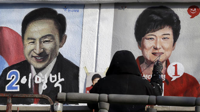 A painter paints  President-elect Park Geun-hye of ruling Saenuri Party, right, and President Lee Myung-bak, left, at Korean Civic Education Institute for Democracy in Seoul, South Korea, Thursday, Dec. 20, 2012. The wall painting is part of renovation work for the building as well as publicizing the 18th Presidential Election which elected Park as the country's first female president. (AP Photo/Lee Jin-man)