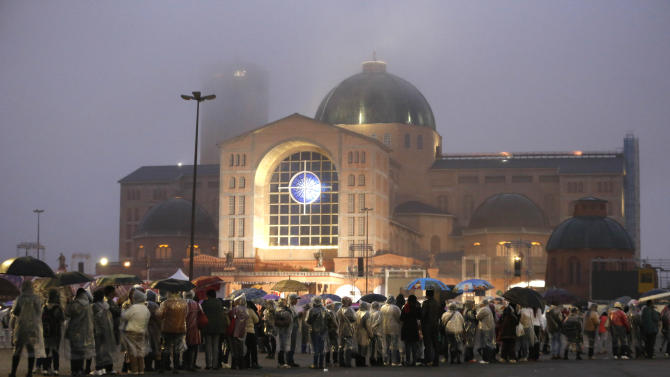Pilgrims wait under the rain outside the Aparecida basilica for the arrival of Pope Francis in Aparecida, Brazil, Wednesday, July 24, 2013. Thousands packed into the huge basilica, and tens of thousands more braved a cold rain outside to catch a glimpse of the first pope from the Americas returning to a shrine of great meaning to the continent and to him personally. (AP Photo/Victor R. Caivano)