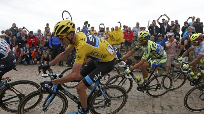Team Sky rider Froome of Britain, race leader and yellow jersey holder, and Tinkoff-Saxo rider Contador of Spain cycle on a cobble-stoned section during the 4th stage of the 102nd Tour de France cycling race from Seraing in Belgium to Cambrai