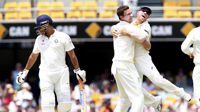 Australia's Josh Hazlewood, centre, celebrates with David Warner, right, after getting the wicket of India's MS Dhoni, left, during their match on day four of the second cricket test in Brisbane, Australia, Saturday, Dec. 20, 2014. (AP Photo/Tertius Pickard)
