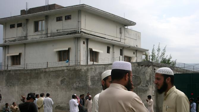 FILE - In this May 5, 2011 file photo, local residents and media are seen outside the house where al-Qaida leader Osama bin Laden was caught and killed in Abbottabad, Pakistan. The courier who led U.S. intelligence to bin Laden's hideout in Pakistan hailed from the Swat Valley, a one-time stronghold of militant Taliban fighters, Pakistani officials said on Wednesday, June 1, 2011. The officials identified the courier as Ibrahim Saeed Ahmed. He and his brother Abrar were shot dead in the daring U.S. Navy SEAL raid May 2 that also killed bin Laden and two other people. (AP Photo/Aqeel Ahmed, File)