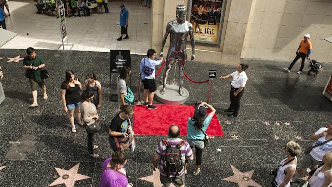 FILE - In this file photo taken Aug. 17, 2012, tourists take photos with a 10-foot statue created and modeled after English soccer star David Beckham displayed in the Hollywood section of Los Angeles. The intersection of Hollywood and Highland is the crossroads for the Hollywood Walk of Fame, where more than 2,400 terrazzo-and-brass stars containing the biggest names in the entertainment business can be viewed by just walking down the sidewalk. (AP Photo/Damian Dovarganes, File)