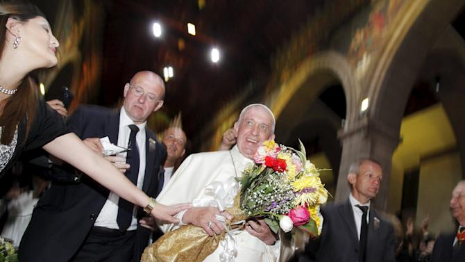 Pope Francis as he walks with a bouquet of flowers inside the Metropolitan Cathedral of Quito in Quito, Ecuador
