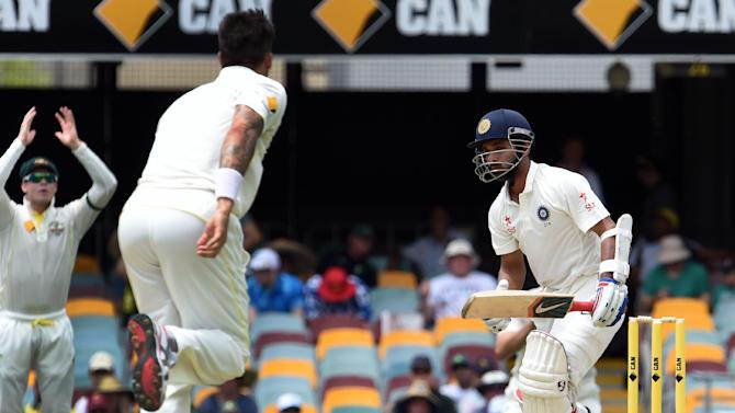 India's Ajinkya Rahane (R) fails to play a quick delivery by Australia's paceman Mitchell Johnson (C) on the fourth day of the 2nd cricket Test match between Australia and India at Gabba in Brisbane on December 20, 2014