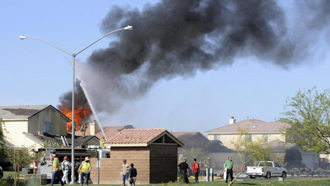 Smoke and flames rise after a Marine jet crashed into a residential area in the desert community of Imperial, Calif., setting two homes on fire Wednesday, June 4, 2014. The pilot ejected safely, and there was no immediate word of any injuries on the ground. The Harrier AV-8B went down at 4:20 p.m. in Imperial, a city of about 15,000 near the U.S.-Mexico border about 90 miles east of San Diego. (AP Photo/Imperial Valley Press, Chelcey Adami)