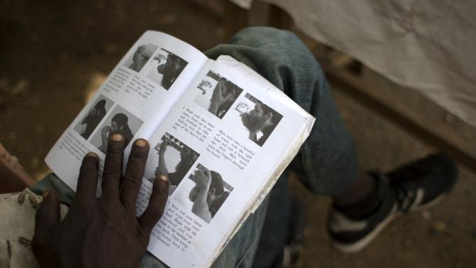 In this Sept. 28, 2012 photo, a man reads about Islamic customs and traditions at the Al-Fattah Mosque before the start of Friday prayer in Gressier, Haiti. Islam has won a growing number of followers in this impoverished country, especially after the catastrophic earthquake in 2010 that killed hundreds of thousands and left millions more homeless. (AP Photo/Dieu Nalio Chery)