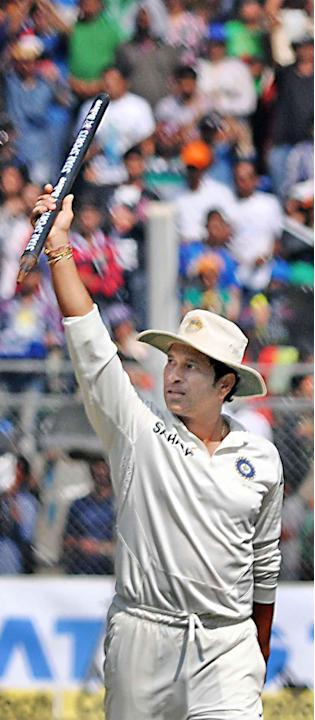 Cricket legend Sachin Tendulkar celebrates after winning the Test match series against West Indies on the third day of the second Test his last and 200th Test at the Wankhede Stadium in Mumbai on Nov.