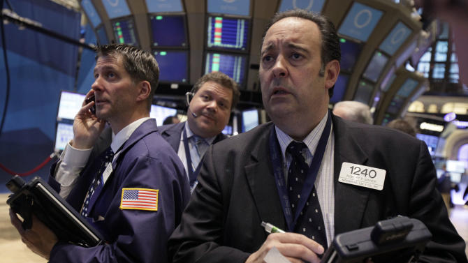 Robert Maher, right, works with fellow traders on the floor of the New York Stock Exchange, Friday, May 11, 2012, in New York. Financial stocks are leading the market lower in early trading after JPMorgan Chase disclosed a huge trading loss. (AP Photo/Richard Drew)