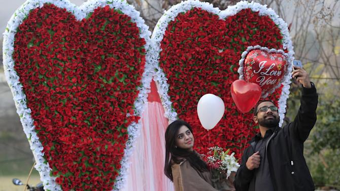 A couple takes a selfie as they stand next to a heart-shaped paper flower decoration at flower market on Valentine's Day in Islamabad