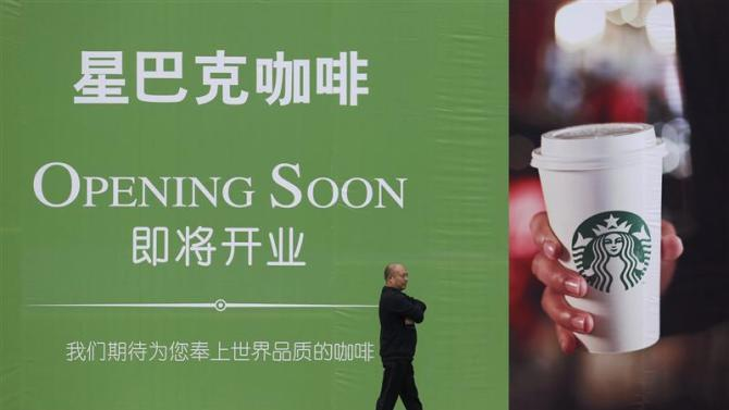 File photo of a man walking past an advertisement board of Starbucks in Wuhan