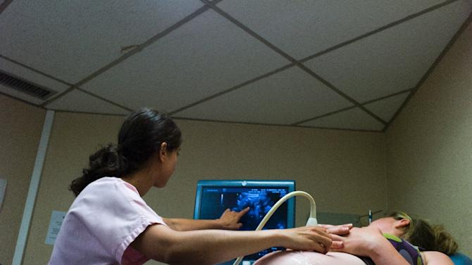 A doctor shows a patient results from an ultrasound
