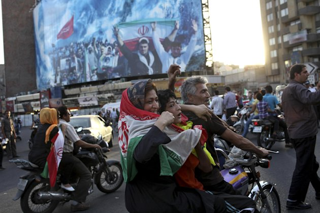 Iranians attend a street celebration, in Tehran, after their national soccer team qualified for the Brazil 2014 World Cup, after defeating South Korea, on Tuesday, June 18, 2013. The win set off wild