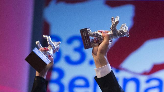 The arms of actress Paulina Garcia, left, with her Silver Bear Best Actress award for her role in Gloria and cameraman Aziz Zhambakiyev with his Silver Bear Best Camera award for his work in the film Harmony Lessons at the closing ceremony at the 63rd edition of the Berlinale, International Film Festival in Berlin, Saturday, Feb. 16, 2013. (AP Photo/Gero Breloer)