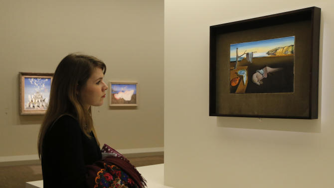 """In this photo taken Monday Nov. 19, 2012, a visitor looks at the painting 'La Persistance de la Memoire, 1931', by Spanish artist Salvador Dali (1904-1989) during the presentation to the press of the exhibition """"Dali"""" at the Centre Pompidou modern art museum, in Paris. A major retrospective of Salvador Dali in Paris aims to rewrite the art history books, reconciling for the first time the last decades of his life _ when he was accused of money-making self-publicity through numerous television appearances _ with his earlier, respected Surrealist period. (AP Photo/Francois Mori)"""