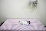 "A baby abandoned in a ""baby box"" at Joosarang church waits for a medical examination at a children's hospital in Seoul September 19, 2012. REUTERS/Kim Hong-Ji"
