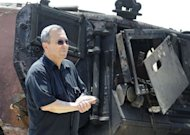 "Israeli Defence Minister Ehud Barak inspects a burnt armoured vehicle near the Kerem Shalom border crossing after unidentified gunmen crossed into Israel. Egypt's army vowed Monday to ""avenge"" the killing of 16 troops by gunmen near the Israeli border and President Mohamed Morsi won US backing as he ordered his security forces to take full control of the Sinai"