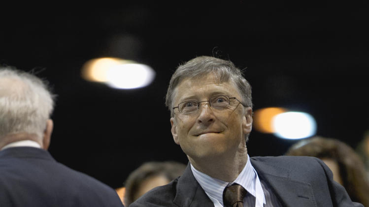 Bill Gates, a director with Berkshire Hathaway, tosses a newspaper during a newspaper tossing competition  in Omaha, Neb., Saturday, May 5, 2012. Berkshire Hathaway is holding it's annual shareholders meeting this weekend. (AP Photo/Nati Harnik)