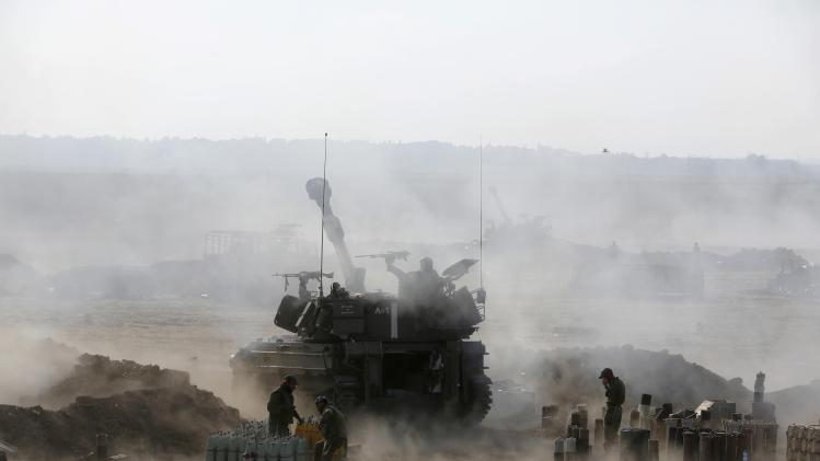 An Israeli mobile artillery unit fires towards the Gaza Strip