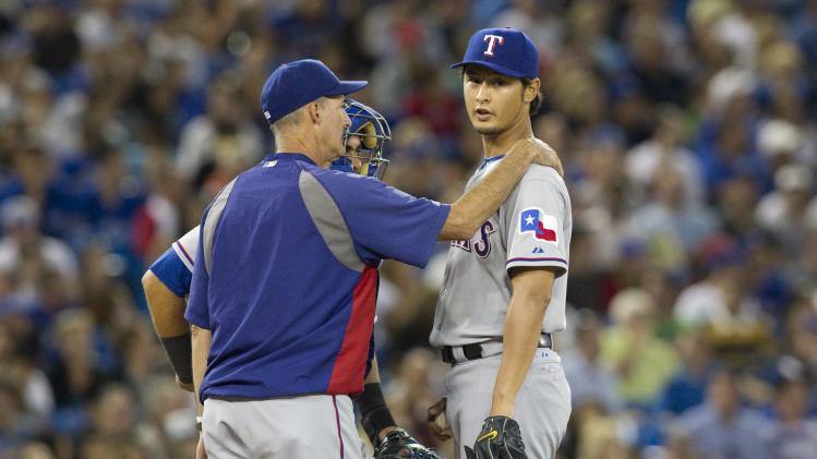 Texas Rangers pitching coach Mike Maddux, left, speaks to pitcher Yu Darvish, right, after Toronto Blue Jays' Rajai Davis hit an RBI during the fifth inning of baseball game action in Toronto, Friday, Aug. 17 , 2012. (AP Photo/The Canadian Press, Chris Young)