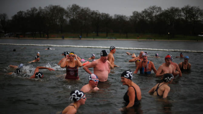 Members of Serpentine swimming club catch their breath after completing annual Christmas Day race in the Serpentine River in central London