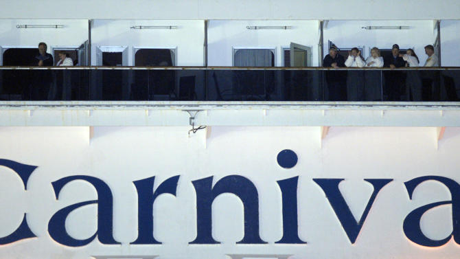 People watch from their balconies aboard the Carnival Triumph after it was towed to the cruise terminal in Mobile, Ala., Thursday, Feb. 14, 2013. The ship with more than 4,200 passengers and crew members idled for nearly a week in the Gulf of Mexico following an engine room fire. (AP Photo/G M Andrews)