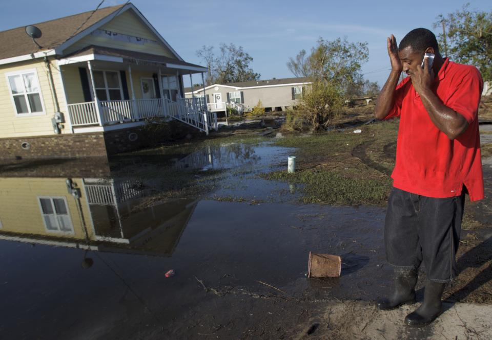 Ron Steward wipes his brow next to the house of his mother, Clara Williams, in Ironton, La., which was flooded from Hurricane Isaac, near Louisiana Hwy 23 in Plaquemines Parish, Monday, Sept. 3, 2012. The house was built seven years ago after her previous home was destroyed by Hurricane Katrina. (AP Photo/Matthew Hinton)