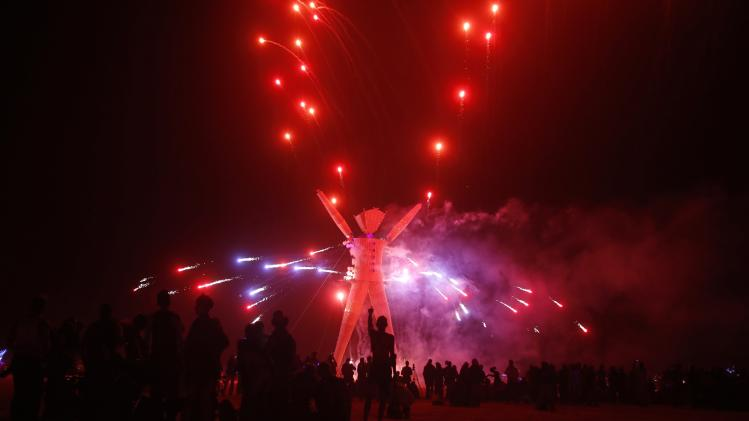 "Fireworks are seen before the Man burns during the Burning Man 2014 ""Caravansary"" arts and music festival in the Black Rock Desert of Nevada"