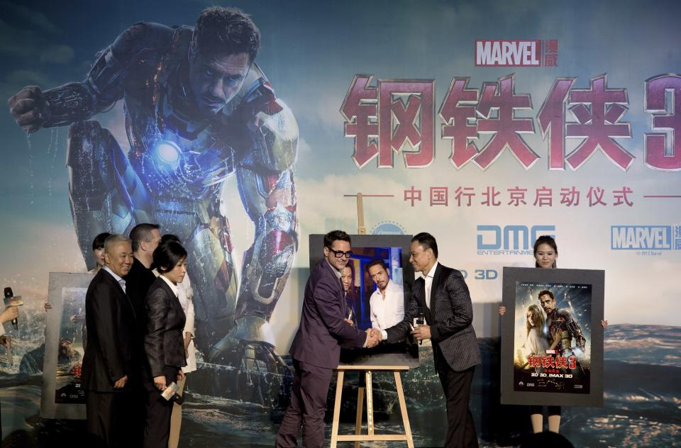 "U.S. actor Robert Downey Jr. center, shakes hands with Chinese actor Wang Xueqi after a photo session during a world premiere event of his new movie ""Iron Man 3"" at a Beijing hotel Saturday, April 6, 2013. (AP Photo/Andy Wong)"